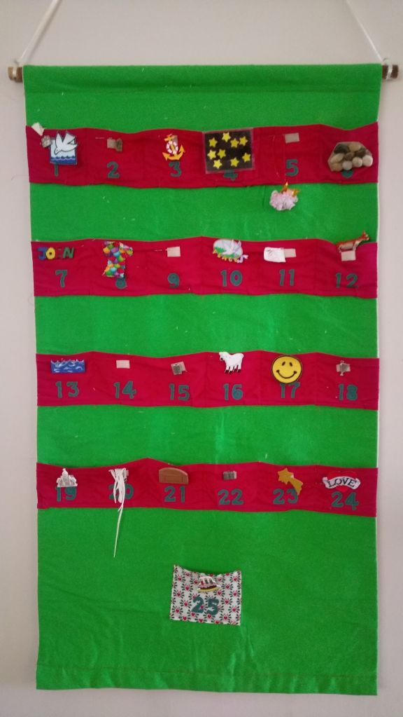 Homemade green material advent calendar with red pockets
