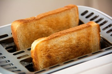 2 pieces of toast popping out of a toaster