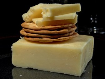 small bits of cheese on water crackers on a larger block of cheese