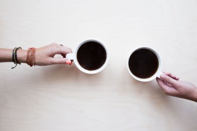 two hands holding onto a coffee cup each
